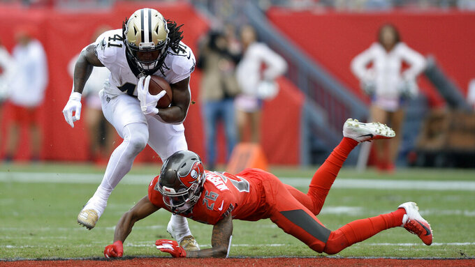 New Orleans Saints running back Alvin Kamara (41) steps over a tackle by Tampa Bay Buccaneers defensive back Sean Murphy-Bunting (26) during the first half of an NFL football game Sunday, Nov. 17, 2019, in Tampa, Fla. (AP Photo/Jason Behnken)