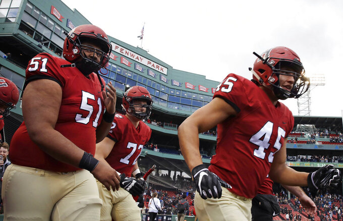 Harvard offensive lineman Justin Hunter (51) and linebacker Jake Brown (45) take to the field prior to the opening kick-off during an NCAA college football game at Fenway Park in Boston, Saturday, Nov. 17, 2018. (AP Photo/Charles Krupa)