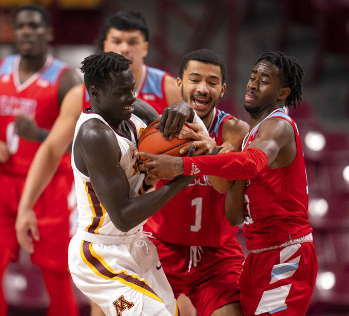 Minnesota guard Both Gach, left, wrestles for the ball with Loyola Marymount guard Dameane Douglas (1) and Jalin Anderson, right, in the first half of an NCAA college basketball game Monday, Nov. 30, 2020, in Minneapolis. (Jeff Wheeler/Star Tribune via AP)