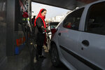 A woman fills her car at a gas station in Tehran, Iran, Friday, Nov. 15, 2019. Authorities have imposed rationing and increased the prices of fuel. The decision came following months of speculations about possible rationing after the U.S. in 2018 reimposed sanctions that sent Iran's economy into free-fall following Washington withdrawal from 2015 nuclear deal between Iran and world powers. (AP Photo/Vahid Salemi)