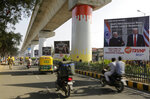 In this Feb. 21, 2020, photo, commuters move past hoardings welcoming U.S. President Donald Trump near Sardar Patel stadium in Ahmedabad, India. A festive mood has enveloped Ahmedabad in India's northwestern state of Gujarat ahead of Prime Minister Narendra Modi's meeting Monday with U.S. President Donald Trump, whom he's promised millions of adoring fans. The rally in Modi's home state may help replace his association with deadly anti-Muslim riots in 2002 that landed him with a U.S. travel ban. It may also distract Indians, at least temporarily, from a slumping economy and ongoing protests over a citizenship law that excludes Muslims, but also risks reopening old wounds. (AP Photo/Ajit Solanki)