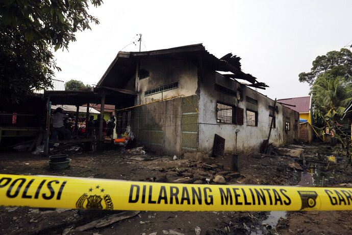 Police tape is set up around a match factory after a fire in Langkat, North Sumatra, Indonesia, Friday, June 21, 2019. A number of people including children were killed in the fire that swept through a house that doubled as a match factory, a disaster official said Friday. (AP Photo)