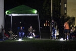 Neighbors remain outdoors using camping tents and portable lights for fear of possible aftershocks on their first night after a 6.4-magnitude earthquake struck in Guanica, Puerto Rico, Tuesday, Jan. 7, 2020. The quake was followed by a series of strong aftershocks, part of a 10-day series of temblors spawned by the grinding of tectonic plates along three faults beneath southern Puerto Rico. (AP Photo/Carlos Giusti)