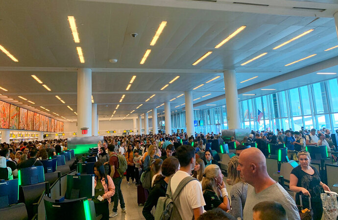 In this photo provided by Twitter user Brenna but in Leo Season, travelers stand in long lines to clear customs at John F. Kennedy International Airport, Friday, Aug. 16, 2019, in New York, due to a temporary computer outage that affected U.S. Customs and Border Protection. (Brenna but in Leo Season via AP)