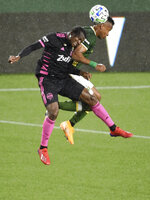 Seattle Sounders defender Nouhou Tolo, left, and Portland Timbers forward Jeremy Ebobisse, right, go up for a header during the first half of an MLS soccer match in Portland, Ore., Wednesday, Sept. 23, 2020. (AP Photo/Steve Dykes)