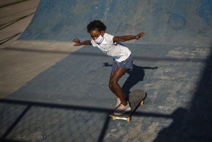 "Sulamita Fernandes, 7, takes skateboard class from the NGO ""CDD Skate Arte,"" at a public skate park in the City of God favela of Rio de Janeiro, Brazil, Thursday, Aug. 5, 2021. (AP Photo/Bruna Prado)"
