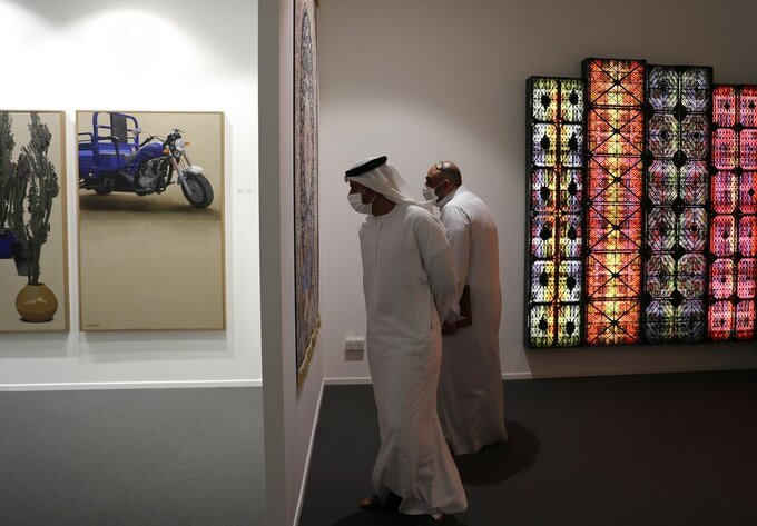 People visit the 14th edition of Art Dubai at Dubai International Financial Centre, DIFC, which features 50 galleries from 31 countries with a focus on modern and contemporary art, in Dubai, United Arab Emirates, Tuesday, March 30, 2021. (AP Photo/Kamran Jebreili)