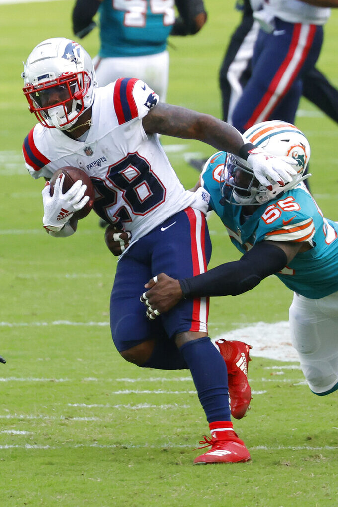 Miami Dolphins outside linebacker Jerome Baker (55) brings down New England Patriots running back James White (28), during the first half of an NFL football game, Sunday, Dec. 20, 2020, in Miami Gardens, Fla. (AP Photo/Joel Auerbach)