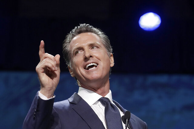 FILE - In this June 1, 2019, file photo, Gov. Gavin Newsom speaks during the 2019 California Democratic Party State Organizing Convention in San Francisco. Gov. Newsom is wrapping up a first year highlighted by the bankruptcy of the country's largest utility, an escalating homelessness crisis and an intensifying feud with the Trump administration, along with record-low unemployment and a booming state economy producing a multi-billion-dollar surplus. (AP Photo/Jeff Chiu, File)