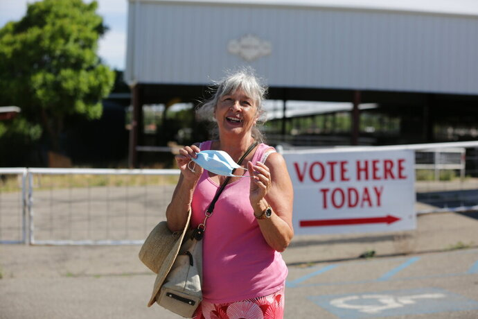 A voter adjusts her mask as she leaves a polling station on the fringe of a rodeo grounds primary voting on Tuesday, June 2, 2020, in Santa Fe, New Mexico. Inside, poll workers wore similar surgical masks and squirted sanitizing gel into the hands of each voter. (AP Photo/Cedar Attanasio)