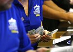 Ticket writers count cash before opening of Monmouth Park Sports Book at Monmouth Park Racetrack. Thursday, June 14, 2018 in Oceanport, NJ. (AP Photo/Noah K. Murray)