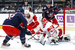 Detroit Red Wings' Thomas Greiss, front right, makes a save as teammate Joe Valeno, left center, and Columbus Blue Jackets' Alexandre Texier, left, and Cam Atkinson look for the rebound during the second period of an NHL hockey game Tuesday, April 27, 2021, in Columbus, Ohio. (AP Photo/Jay LaPrete)