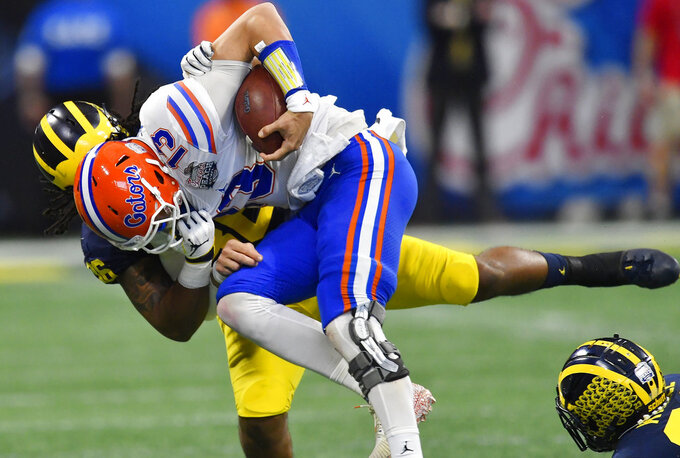 Michigan linebacker Devin Gil (36) tackles Florida quarterback Feleipe Franks (13) during the first half of the Peach Bowl NCAA college football game, Saturday, Dec. 29, 2018, in Atlanta. (AP Photo/Mike Stewart)