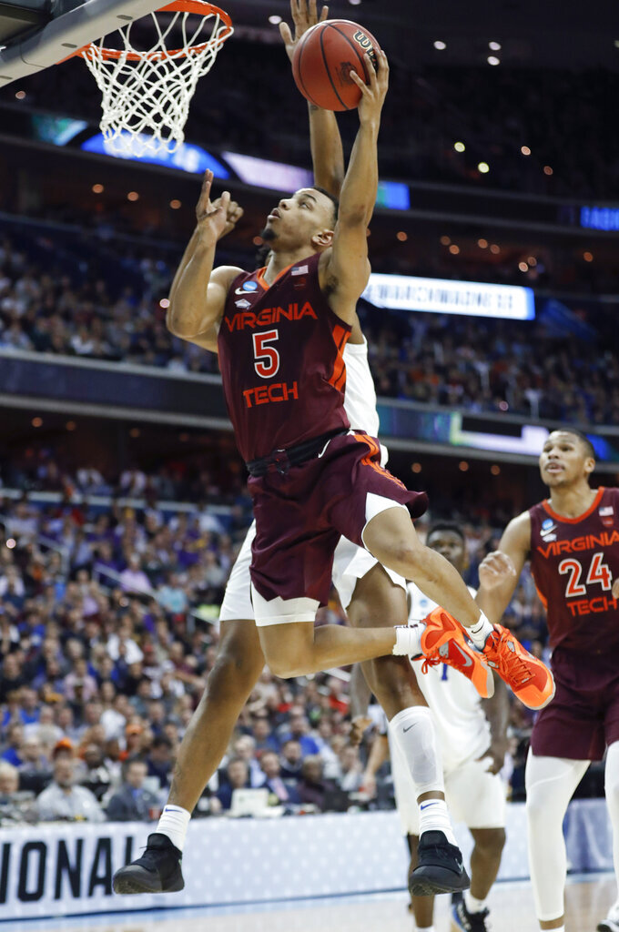 Virginia Tech guard Justin Robinson (5) scores on Duke center Marques Bolden during the second half of an NCAA men's college basketball tournament East Region semifinal in Washington, Friday, March 29, 2019. (AP Photo/Patrick Semansky)
