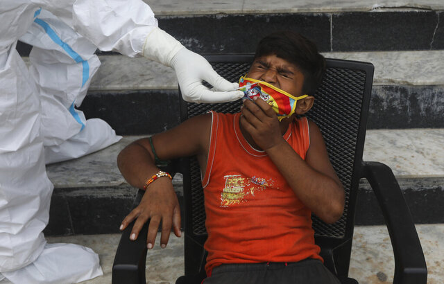 A child grimaces as a health worker takes a nasal swab sample for COVID- 19 testing through rapid antigen methodology, in New Delhi, India , Friday, Aug. 7, 2020. As India hit another grim milestone in the coronavirus pandemic on Friday, crossing 2 million cases and more than 41,000 deaths, community health volunteers went on strike complaining they were ill-equipped to respond to the wave of infection in rural areas. (AP Photo/Manish Swarup)