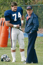 FILE - In this Nov. 2, 1988, file photo, Chicago Bears offensive coordinator Ed Hughes, right, speaks with Jim Covert during NFL football practice in Lake Forest, Ill. Covert made the people he played alongside look good, and after a nearly two-decades-long wait, the tough Chicago Bears left tackle will join them in the Pro Football Hall of Fame. (AP Photo/Mark Elias, File)