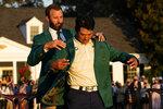 Dustin Johnson helps Hideki Matsuyama, of Japan, put on the champion's green jacket after winning the Masters golf tournament on Sunday, April 11, 2021, in Augusta, Ga. (AP Photo/David J. Phillip)