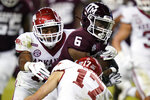 Texas A&M running back Devon Achane (6) breaks a tackle by Arkansas defensive back Hudson Clark (17) during a 30-yard touchdown run against during the second half of an NCAA college football game, Saturday, Oct. 31, 2020, in College Station, Texas. (AP Photo/Sam Craft)