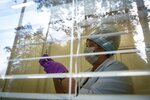 A medical worker preparing a shot of Russia's Sputnik V coronavirus vaccine is seen through a window of a local rural medical post in the village of Ikhala in Russia's Karelia region, Tuesday, Feb. 16, 2021. Russia took pride in being the first country to approve a coronavirus vaccine, although it faced criticism from aboard for doing it before completing the advanced testing necessary to ensure Sputnik V's safety and effectiveness. (AP Photo/Dmitri Lovetsky)