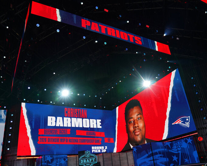 Images are displayed on stage of Christian Barmore, defensive tackle at Alabama, selected by the New England Patriots in the second round of the NFL football draft, Friday, April 30, 2021, in Cleveland. (AP Photo/Tony Dejak)