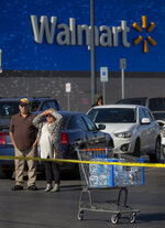 Shoppers look to the scene of a fatal shooting in the parking lot of a Walmart in Duncan, Okla., on Monday, Nov. 18, 2019. (Chris Landsberger/The Oklahoman via AP)
