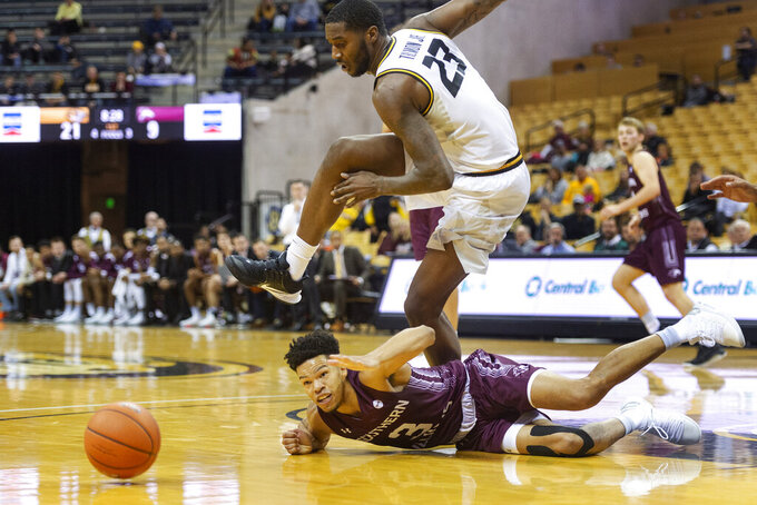 Missouri's Jeremiah Tilmon, top, leaps over Southern Illinois' Ronnie Suggs, bottom, as they battle for the ball during the first half of an NCAA college basketball game Sunday, Dec. 15, 2019, in Columbia, Mo. (AP Photo/L.G. Patterson)