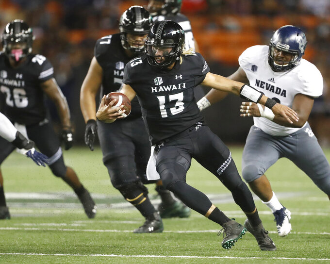 Hawaii quarterback Cole McDonald (13) runs against Nevada during the fourth quarter at an NCAA college football game Saturday, Oct. 20, 2018, in Honolulu. Nevada defeated Hawaii 40-22. (AP Photo/Marco Garcia)