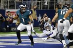 Philadelphia Eagles quarterback Jalen Hurts (1) is pressured behind the line of scrimmage by Dallas Cowboys defensive end Tarell Basham (93) in the first half of an NFL football game in Arlington, Texas, Monday, Sept. 27, 2021. (AP Photo/Michael Ainsworth)