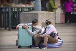 Travelers wearing face masks sit with their luggage outside the Beijing Railway Station in Beijing, Wednesday, March 25, 2020. Some train stations and bus services reopened in China's Hubei Province on Wednesday and people who passed a health check would finally be allowed to travel for the first time since the coronavirus outbreak surged in January. The new coronavirus causes mild or moderate symptoms for most people, but for some, especially older adults and people with existing health problems, it can cause more severe illness or death. (AP Photo/Mark Schiefelbein)