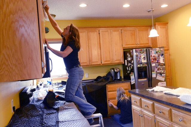 Toni Amenrud, left, and her daughter, Veronica, work in a Brooklyn Park, Minn., kitchen on Monday, June 22, 2020. Amenrud owns a Kitchen Tune-Up franchise. (Scott Takushi/Pioneer Press via AP)