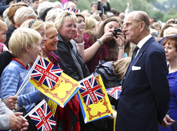 FILE - In this June 7, 2012 file photo, Britain's Prince Philip greets well wishers as he arrives in Perth, Scotland. Prince Philip, the irascible and tough-minded husband of Queen Elizabeth II who spent more than seven decades supporting his wife in a role that both defined and constricted his life, has died, Buckingham Palace said Friday, April 9, 2021. He was 99. (Andrew Milligan/PA via AP)