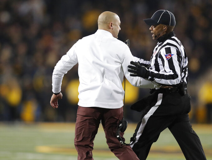Minnesota head coach P.J. Fleck, left, is escorted back to the sideline by an official after running onto the field after a play during the second half of an NCAA college football game against Iowa, Saturday, Nov. 16, 2019, in Iowa City, Iowa. (AP Photo/Matthew Putney)
