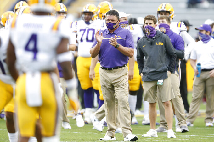 LSU head coach Ed Orgeron, center, watches the team warm up before taking on South Carolina in an NCAA college football game in Baton Rouge, La., Saturday, Oct. 24, 2020. (AP Photo/Brett Duke)