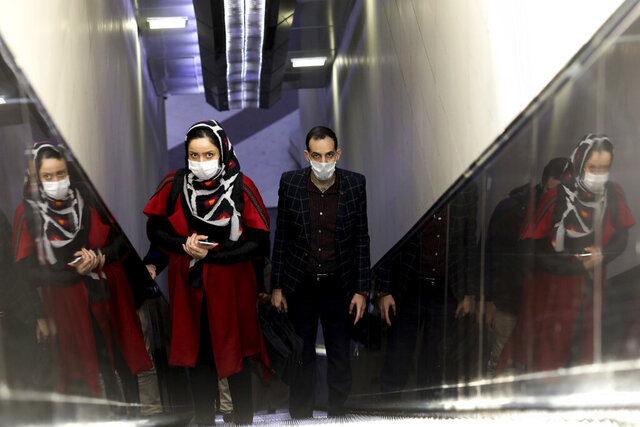 People wear masks to help guard against the Coronavirus as they ride an escalator at a the metro station, in Tehran, Iran, Sunday, Feb. 23, 2020. Iran's health ministry raised Sunday the death toll from the new virus to 8 people in the country, amid concerns that clusters there, as well as in Italy and South Korea, could signal a serious new stage in its global spread. (AP Photo/Ebrahim Noroozi)