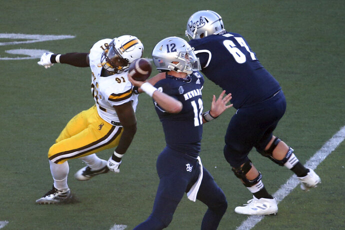 Nevada quarterback Carson Strong (12) throws a touchdown pass against Wyoming State during the first half of an NCAA college football game Saturday, Oct. 24, 2020, in Reno, Nev. (AP Photo/Lance Iversen)