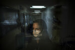 """In this photo created with an in-camera multiple exposure, registered nurse Lisa Lampkin, part of a group of nurses who had been treating coronavirus patients in an intensive care unit, stands for a photo in the empty COVID-19 ICU at Providence Mission Hospital in Mission Viejo, Calif., Tuesday, April 6, 2021. """"I would go home, try to sleep,"""" she says. Then she would """"wake up to the reality of this pandemic again."""" (AP Photo/Jae C. Hong)"""