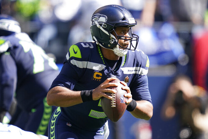Seattle Seahawks quarterback Russell Wilson passes against the Tennessee Titans during the first half of an NFL football game, Sunday, Sept. 19, 2021, in Seattle. (AP Photo/Elaine Thompson)