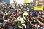 General Manager of Lagos State Emergency Management Agency Tiamiyu Adesina, center, updates the press at the scene of a collapsed building in Lagos, Nigeria, Thursday March 14, 2019. Search and rescue work continues in Nigeria a day after a building containing a school collapsed with scores of children said to be inside. A National Emergency Management Agency spokesman late Wednesday said 37 people had been pulled out alive, with eight bodies recovered from the ruins. (AP Photo/Sunday Alamba)
