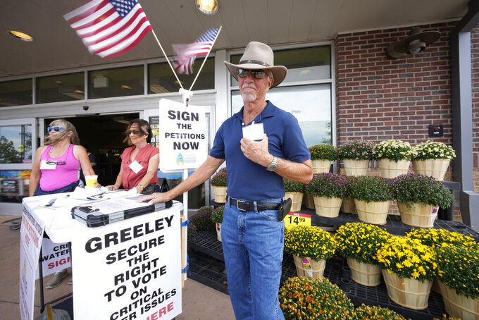 In this Friday, July 23, 2021, photograph, John G. Gauthiere, president of his own civil engineering consulting firm, collects signatures outside a grocery store in west Greeley, Colo.  Figures released this month show that population growth continues unabated in the South and West, even as temperatures rise and droughts become more common. That in turn has set off a scramble of growing intensity in places like Greeley to find water for the current population, let alone those expected to arrive in coming years. (AP Photo/David Zalubowski)