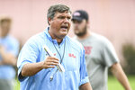 FILE - In this Aug. 9, 2019 ,file photograph, Mississippi head coach Matt Luke talks with offensive linemen during a NCAA college football practice in Oxford, Miss.(Bruce Newman/Oxford Eagle via AP, File)