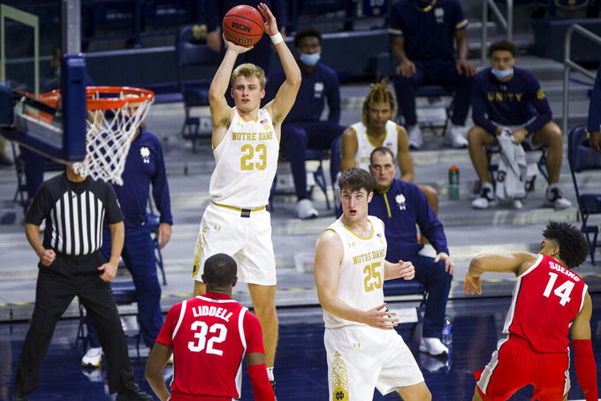 Notre Dame's Dane Goodwin (23) shoots a 3-pointer in front of Ohio State's E.J. Liddell (32) during the second half of an NCAA college basketball game Tuesday, Dec. 8, 2020, in South Bend, Ind. Ohio State won 90-85. (AP Photo/Robert Franklin)