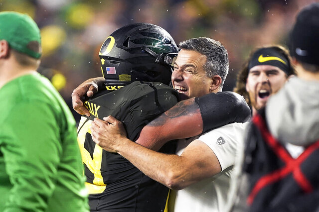 FILE - In this Dec. 6, 2018, file photo, Oregon coach Mario Cristobal, right, celebrates with offensive lineman Shane Lemieux (68) after Oregon defeated Utah 37-15 in an NCAA college football game for the Pac-12 Conference championship, in Santa Clara, Calif. Cristobal was named The Associated Press Pac-12 Coach of the Year Thursday, Dec. 12, 2019. (AP Photo/Tony Avelar, File)