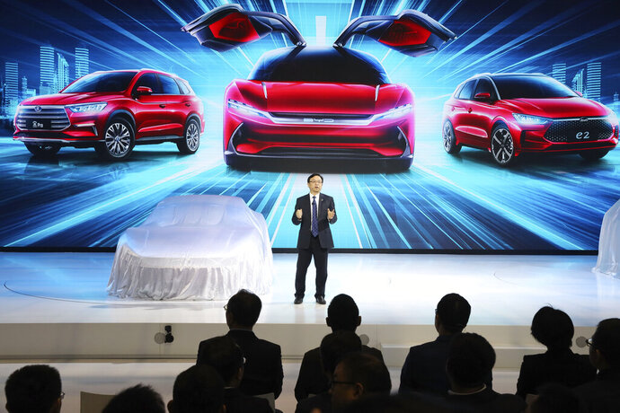 FILE - In this April 16, 2019, file photo, Wang Chuanfu, chairman and president of BYD Auto, the biggest global electric brand by sales volume, prepares to show the latest cars during the Auto Shanghai 2019 show in Shanghai. China's auto sales fell 7.8% in June amid a trade fight with Washington and slower economic growth, extending a year-old contraction that is squeezing automakers that need to spend on developing electric cars. (AP Photo/Ng Han Guan, File)