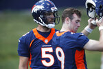 Denver Broncos quarterback Joe Flacco, back, joins quarterback Kevin Hogan during drills at the team's NFL football training facility Wednesday, June 5, 2019, in Englewood, Colo. (AP Photo/David Zalubowski)