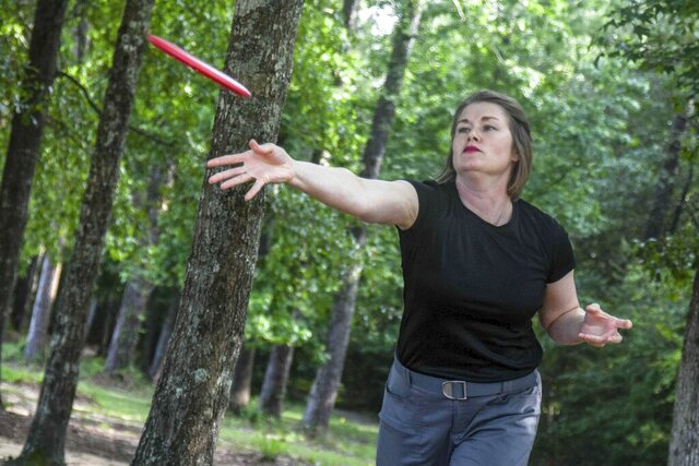 """In this Wednesday May 20, 2020 photo, Deep South Disc Divas member Michelle Clay puts a disc into a basket during practice at Tatum Park in Hattiesburg, Miss. Disc golf, which was started in the 1970s, is much like golf but uses a flying disc and above-ground targets called """"holes."""" (Cam Bonelli/Hattiesburg American via AP)"""