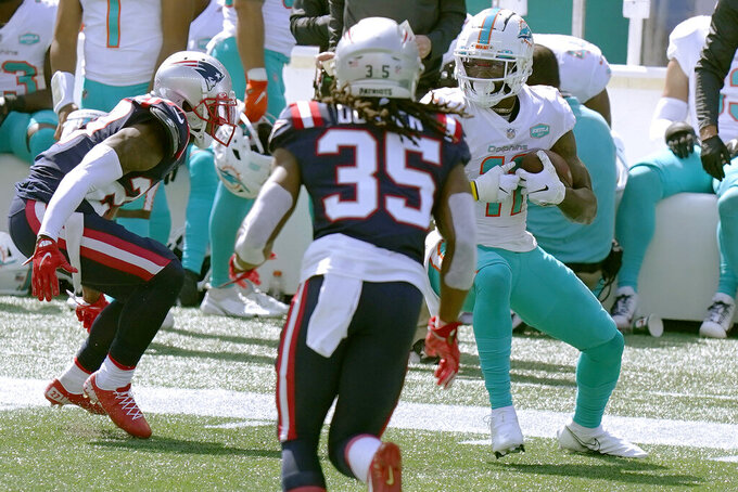 Miami Dolphins wide receiver DeVante Parker, right, looks for room to run after catching a pass against the New England Patriots in the first half of an NFL football game, Sunday, Sept. 13, 2020, in Foxborough, Mass. (AP Photo/Steven Senne)