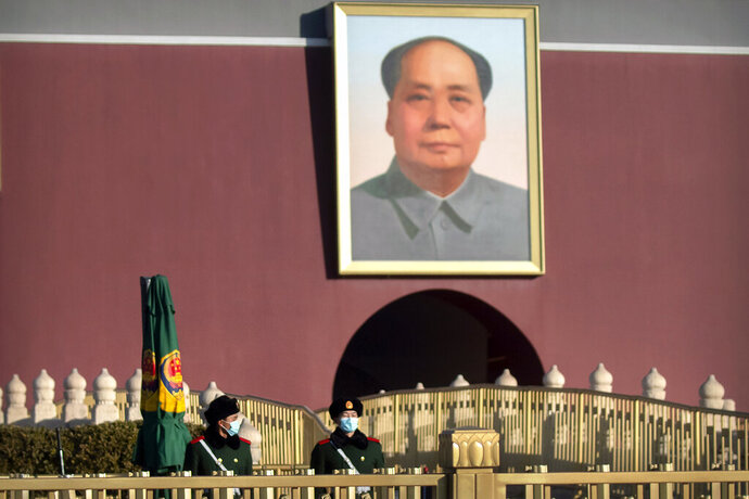Chinese paramilitary police wearing face masks to protect against the spread of the coronavirus stand guard near the portrait of Chinese leader Mao Zedong on Tiananmen Gate near Tiananmen Square in Beijing, Saturday, Jan. 9, 2021. COVID vaccine shots will be free in China, where more than 9 million doses have been give to date, health officials in Beijing said Saturday. (AP Photo/Mark Schiefelbein)