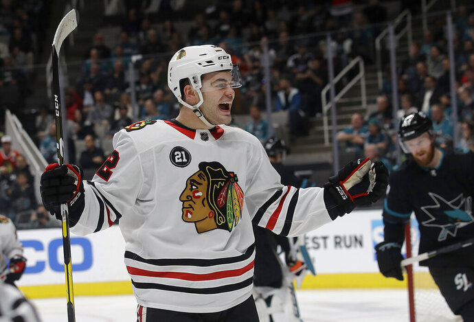 Chicago Blackhawks left wing Alex DeBrincat celebrates after scoring against the San Jose Sharks during the second period of an NHL hockey game in San Jose, Calif., Thursday, March 28, 2019. (AP Photo/Jeff Chiu)