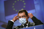 European Commissioner for Crisis Management Janez Lenarcic puts on his face mask at the end of an online media conference at the European Commission headquarters in Brussels, Tuesday, Sept. 22, 2020. Lenarcic said the Commission has increased its stockpile of protective medical equipment and supplies in order to support member states if the health situation deteriorates further in the winter. (AP Photo/Francisco Seco, Pool)