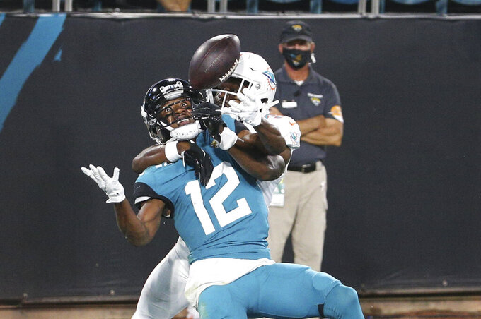 Miami Dolphins cornerback Tae Hayes, right, is called for pass interference as he breaks up a pass intended for Jacksonville Jaguars wide receiver Dede Westbrook during the second half of an NFL football game, Thursday, Sept. 24, 2020, in Jacksonville, Fla. (AP Photo/Stephen B. Morton)